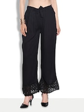 Solid Black Rayon Palazzos With Laced Hem - By